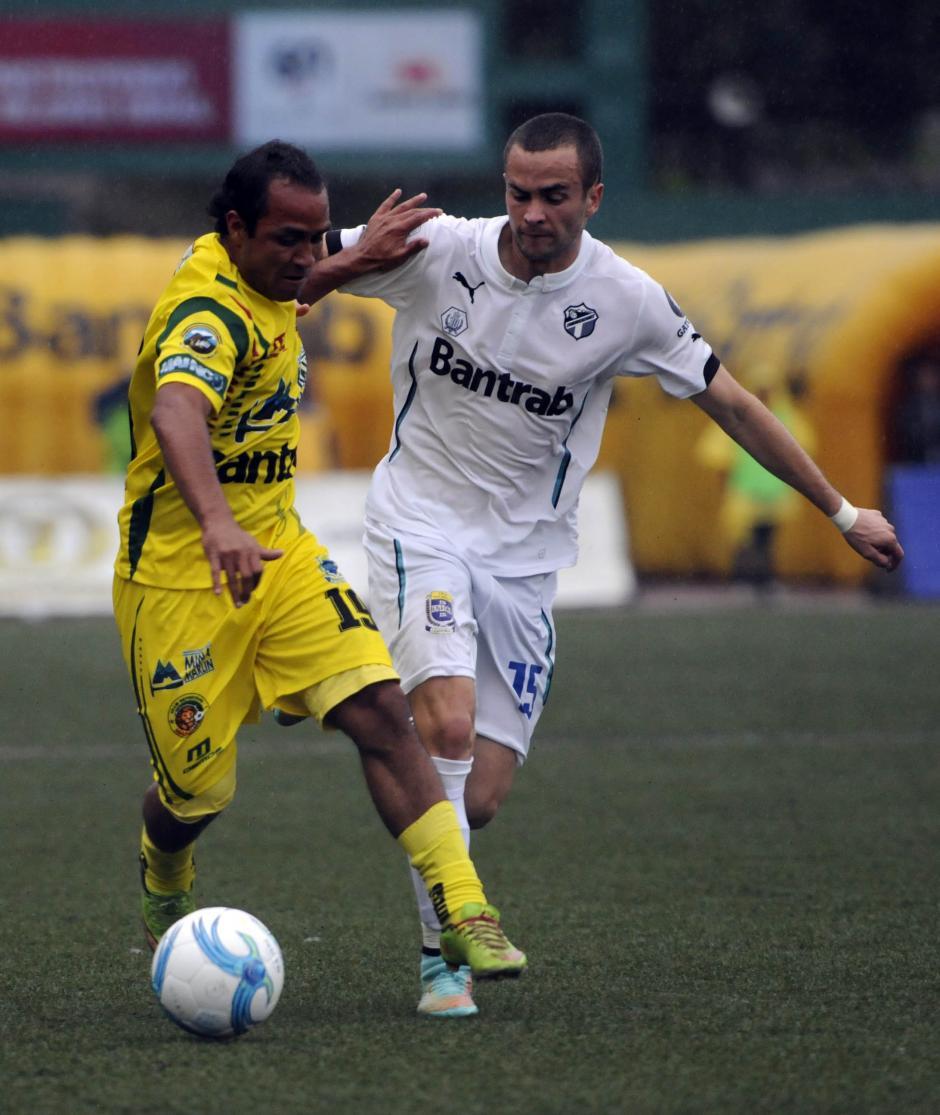 Kevin Norales y Javier Del Águila pelean el balón en el medio campo; en 2011 fueron compañeros de la Selección mundialista. (Foto: Nuestro Diario)