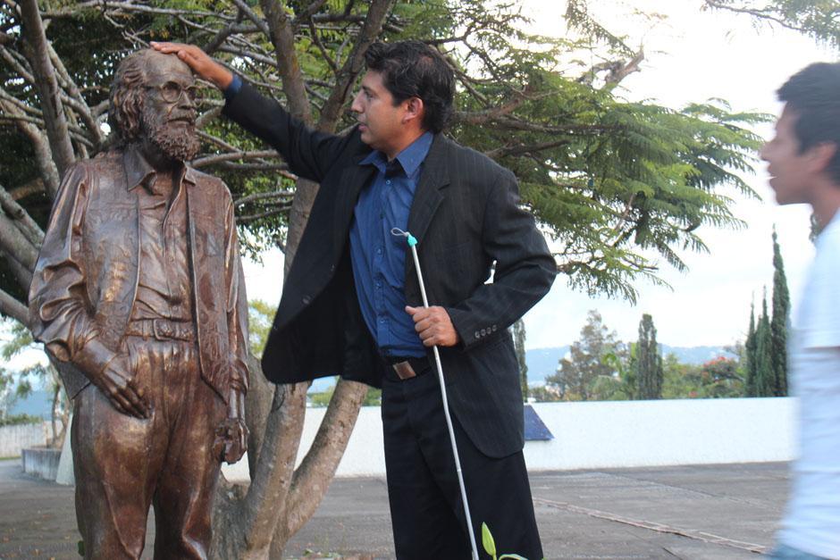 Un joven no vidente se acerca para apreciar el monumento a Efraín Recinos.