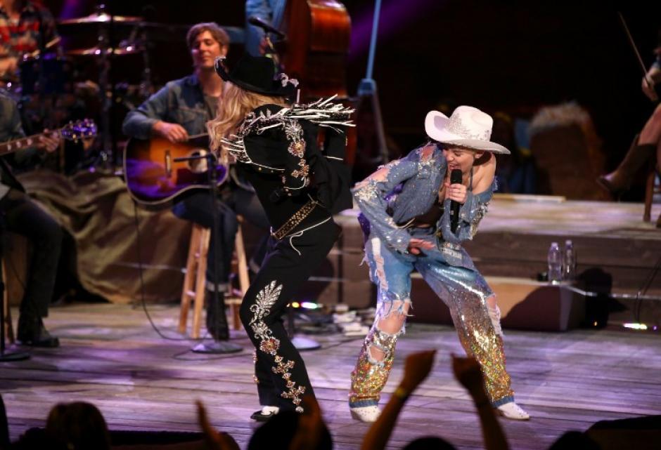 En uno los momentos más destacados de la presentación, Cyrus le dio una nalgada a la Reina del Pop, de 55 años. (Foto: AFP)
