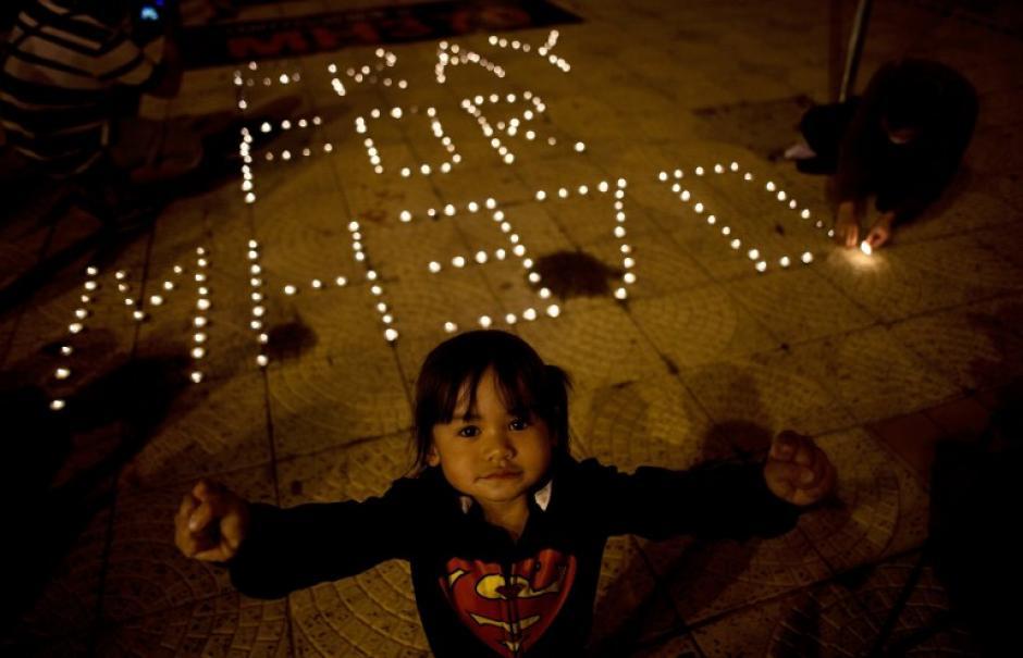 Una niña de Malasia, perteneciente a la etnia china, durante una vigilia realizada por los familiares de los pasajeros