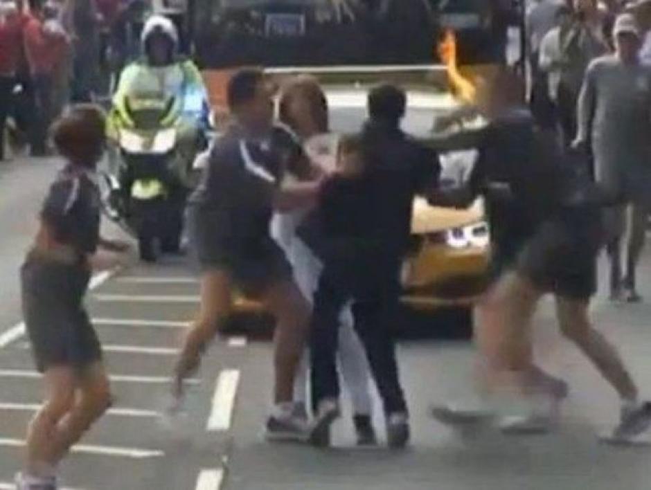 El hombre fue detenido por la Policía al intentar apropiarse por la fuerza de la antorcha. (Captura Youtube)