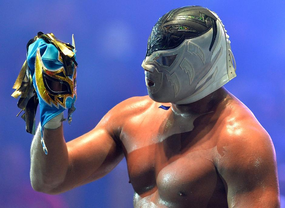 Un luchador sostiene una máscara que arrancó a su adversario