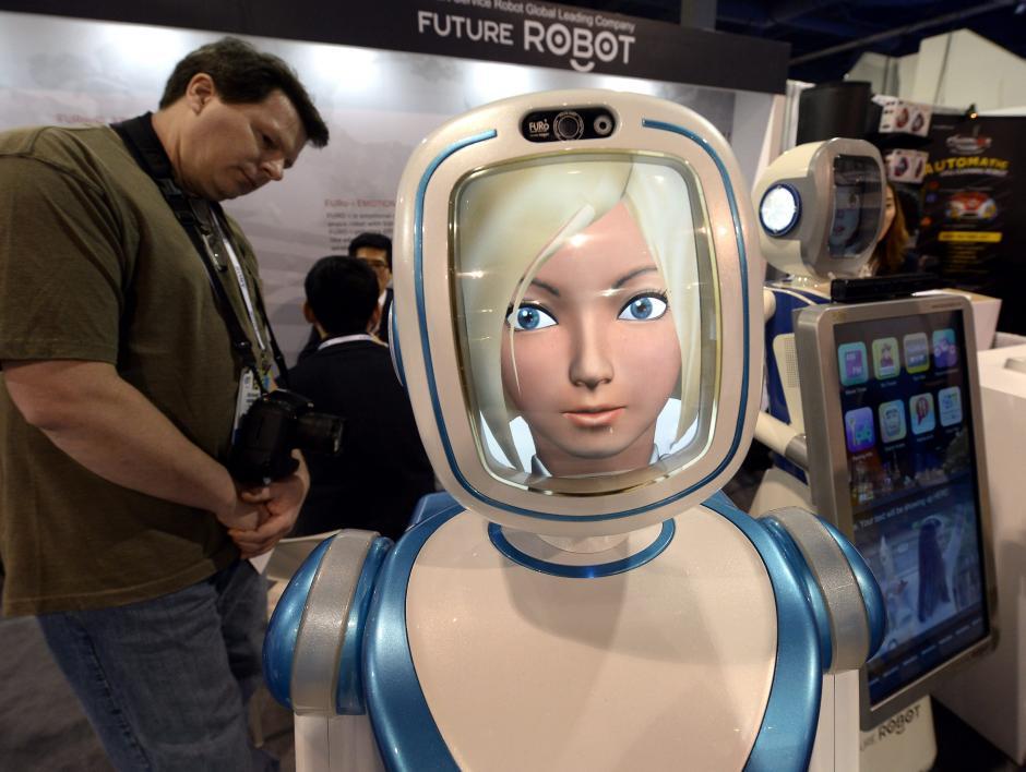 Un asistente observa un robot que ofrece un servicio inteligente las 24 horas, en la Feria Internacional CES. (Foto: EFE/Michael Nelson)