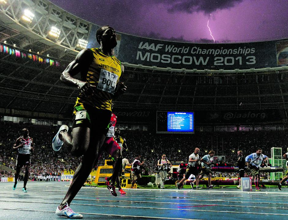Usain Bolt gana los 100 metros finales enelCampeonato del Mundo en el estadio Luzhniki de Moscú el 11 de agosto 2013.Mientras quese observa lacaída de rayos en el cielo.(Foto: AFP/OLIVIER MORIN)