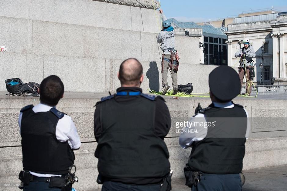 Agentes de la policía esperan a que los miembros de Greenpace bajen de la estatua a Lord Nelson en la Plaza de Trafalgar. (Foto: Leon Neal/AFP)