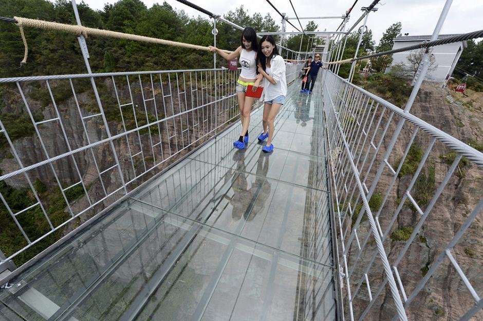 Dos mujeres caminan sobre el puente que es seguro, pero ver hacia abajo hace que sientan la sensación de estar en peligro. (Foto: China Daily)