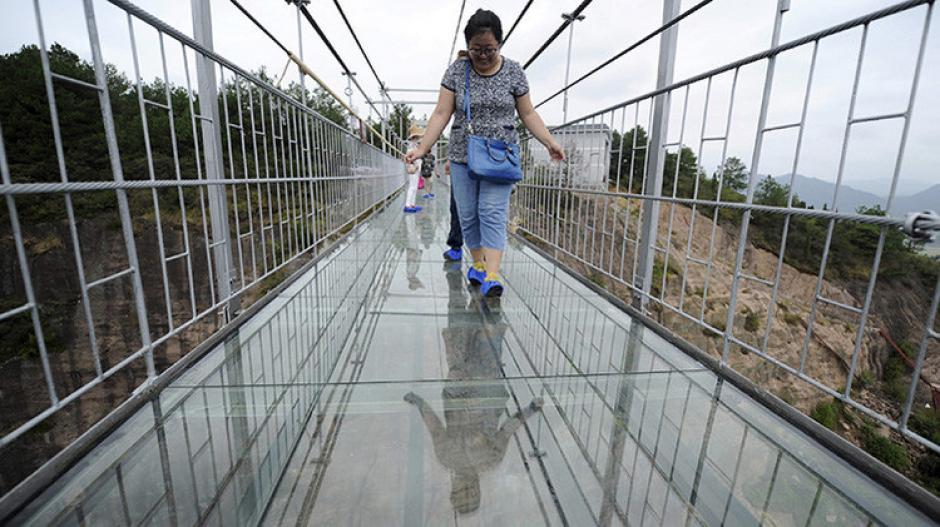 """Los turistas sintieron la curiosidad de ver hacia abajo mientras caminaban por el """"puente de los heróes"""".(Foto: China Daily)"""