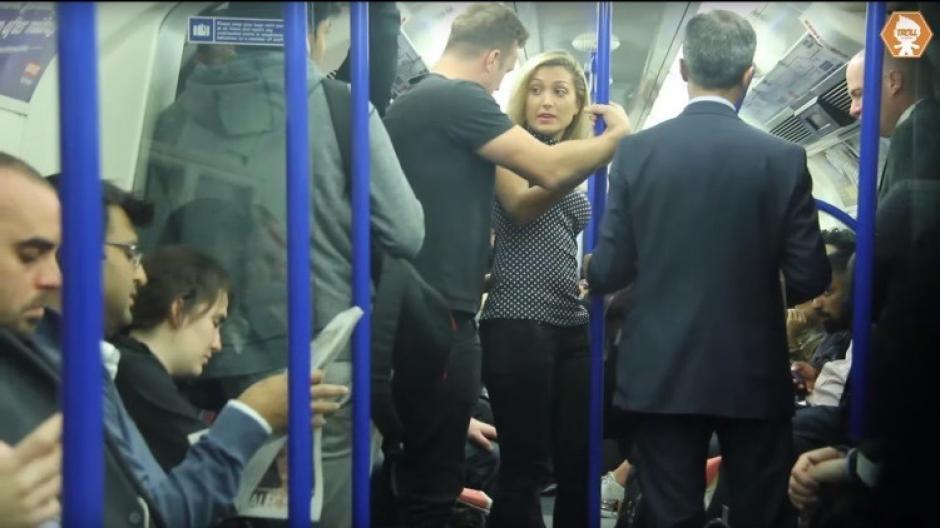 La mujer que iba parada en el metro empieza a sentirse incómoda cuando el hombre con la camiseta negra se le acerca demasiado. (Captura YouTube)