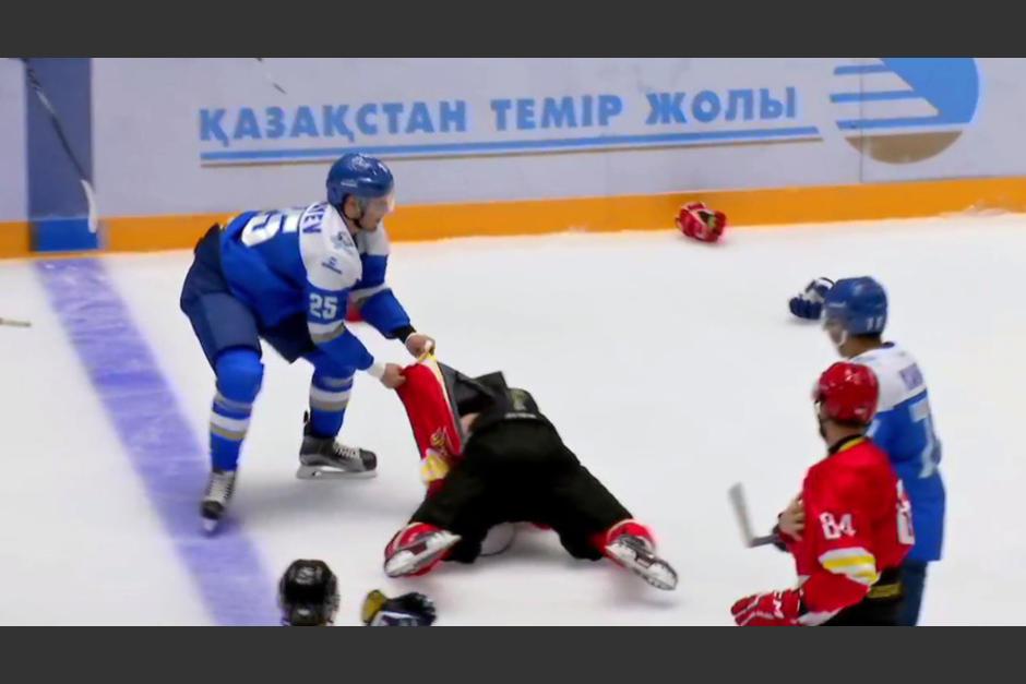 El agresor, de azul, empieza a golpear a cuanto rival encuentra sobre la pista de hielo. (Captura YouTube)