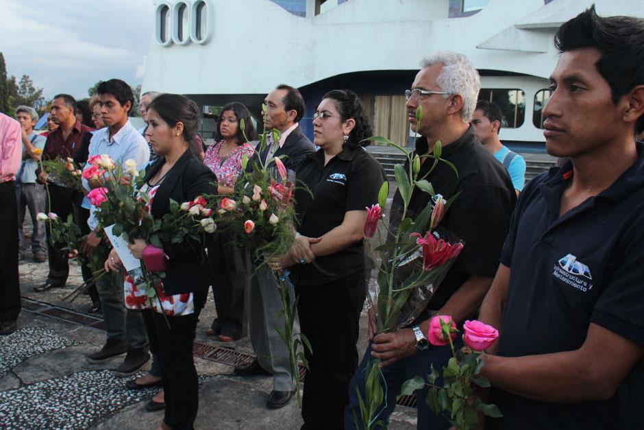Empleados del Teatro Nacional sostienen flores.