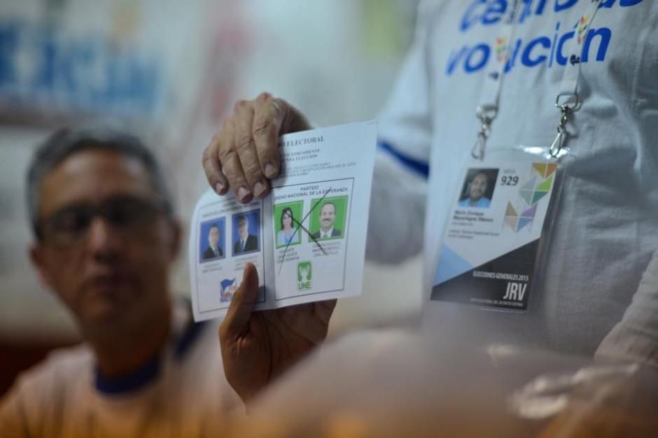El presidente de una de las Juntas Receptoras de Votos, muestra a los fiscales de los partidos políticos, una de las boletas escrutadas.(Foto:Jesús Alfonso/Soy502)