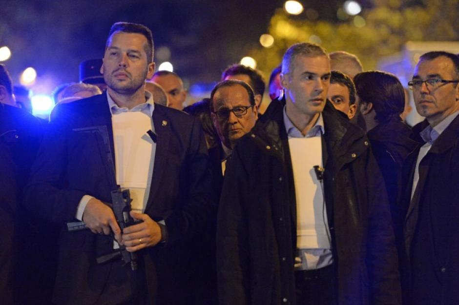 El presidente francés, Francois Hollande (centro con lentes), es evacuado del estadio de fútbol donde presenciaba un juego amistoso entre las selecciones de Francia y Alemania. (Foto: AFP)