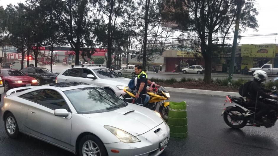 A pesar de la lluvia, Bran acompañó a los agentes que se encuentran en la calzada Roosevelt para regular el tránsito. (Foto: José Hernández)