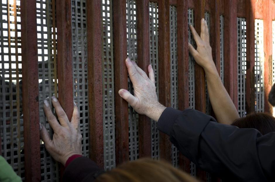 Personas apoyan sus manos contra la valla fronteriza que separa Tijuana (México) y San Diego (EE.UU.). (EFE)
