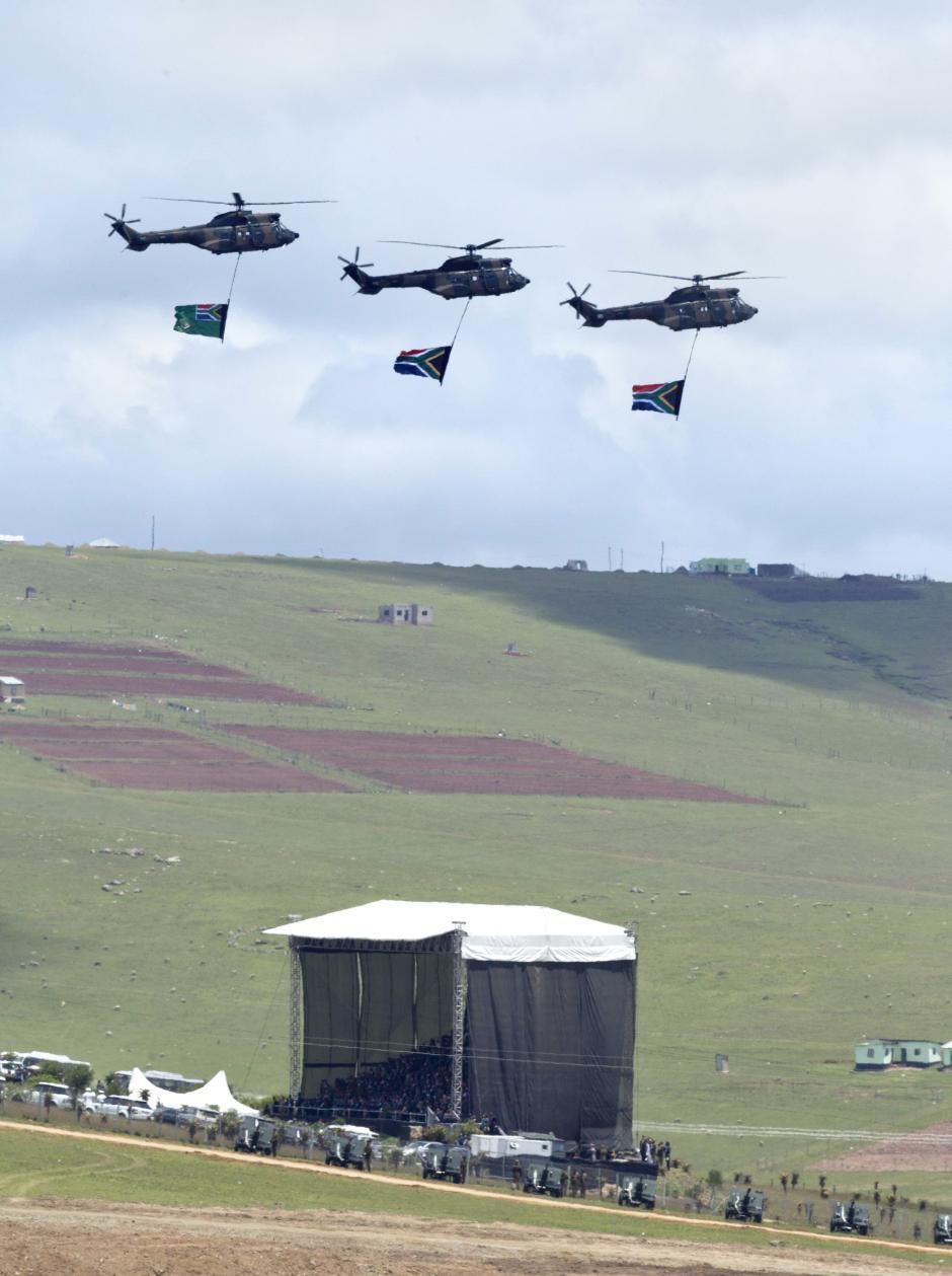Helicópteros de la Fuerza Aérea de Sudáfrica muestran banderas sudafricanas que pasan por encima de la gran carpa donde se desarrolla el funeral de Nelson Mandela. (Foto: EFE)