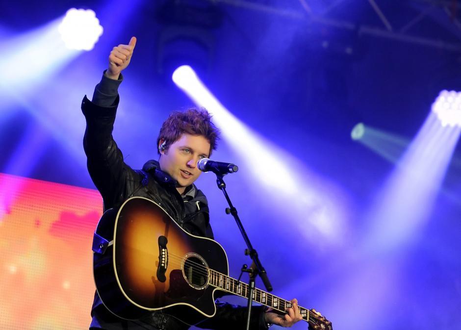 El cantante britanico Nick Howard saluda durante el ensayo de la fiesta de la víspera de Año Nuevo en el Brandenburg Gate en BerlÌn (Alemania). (Foto:EFE/BRITTA PEDERSEN)