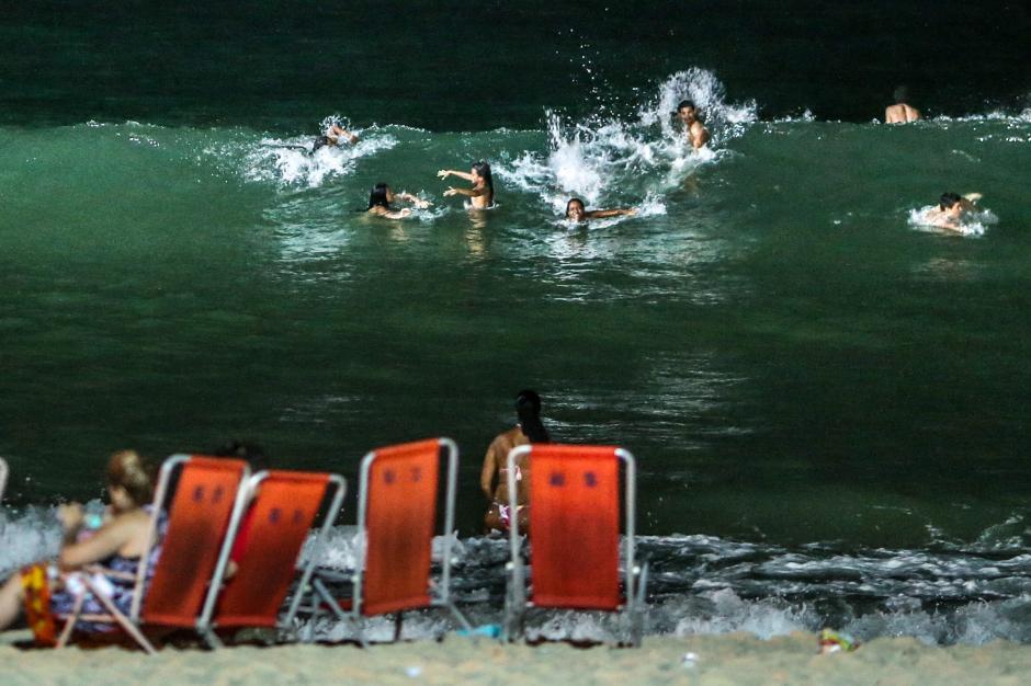 Un grupo de personas se refresca en el mar en la piedra de Arpoador en Río de Janeiro (Brasil). EFE/ Antonio Lacerda