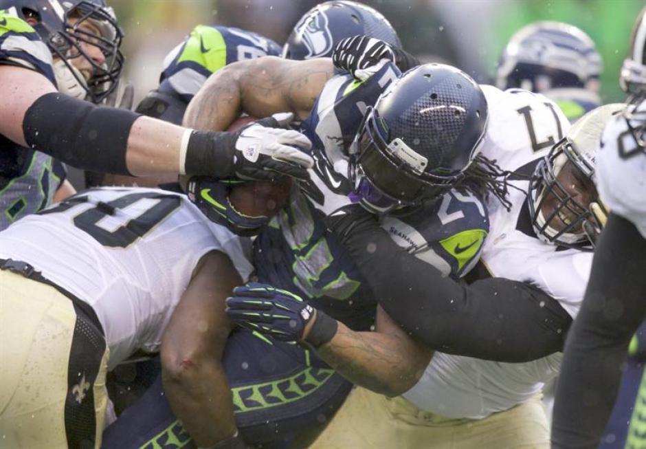 El escolta Marshawn Lynch de los Seahawks de Seattle disputa una yarda extra en el primer tiempo durante el partido contra los Saints de Nueva Orleans el sábado. (Foto: EFE)