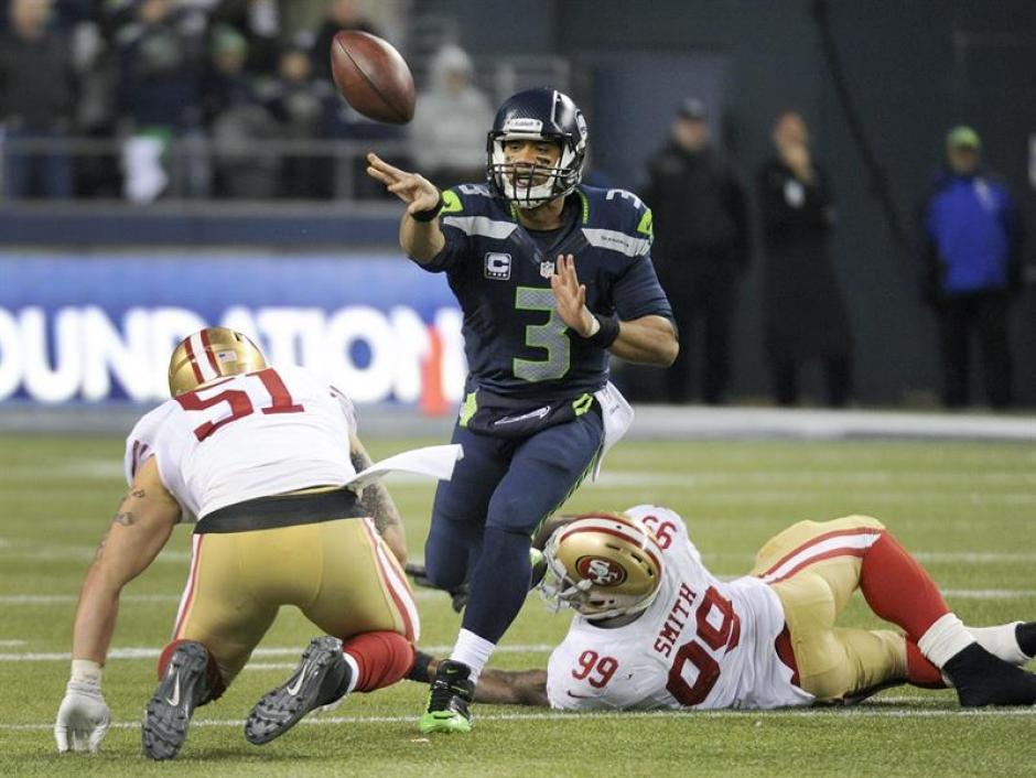 El quarterback de los Seahawks, Russell Wilson lanza un pase, pese a la presión de los jugadores de los 49ers de San Francisco, Aldon Smith y Dan Skuta. (Foto: EFE)