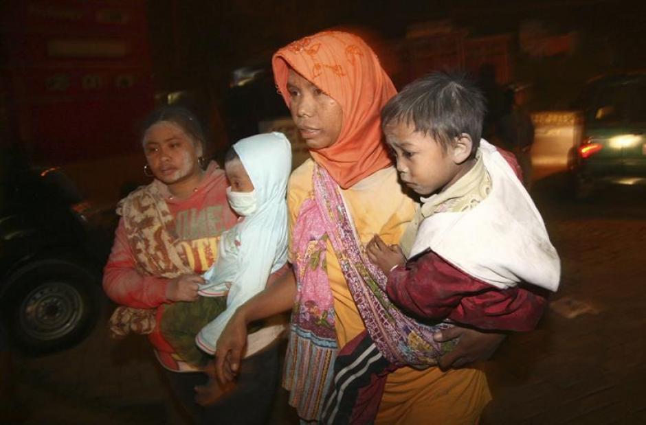 Dos mujeres cargan a sus hijos al momento de la evacuación. Foto:Efe
