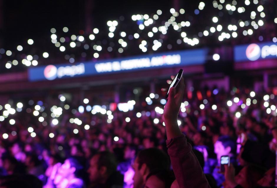 Cientos de espectadores levantan sus teléfonos móviles en honor al músico Gustavo Cerati durante el concierto del grupo chileno La Ley, en la cuarta jornada del Festival. (Foto:EFE/Felipe Trueba)