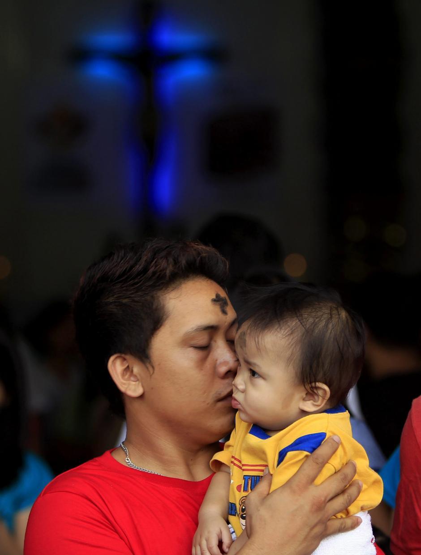 En otros países de denominación católica también los devotos participan en la misa de este miércoles. Aquí una fotografía de un católico cargando a su pequeño hijo en Filipinas. (Foto: EFE)