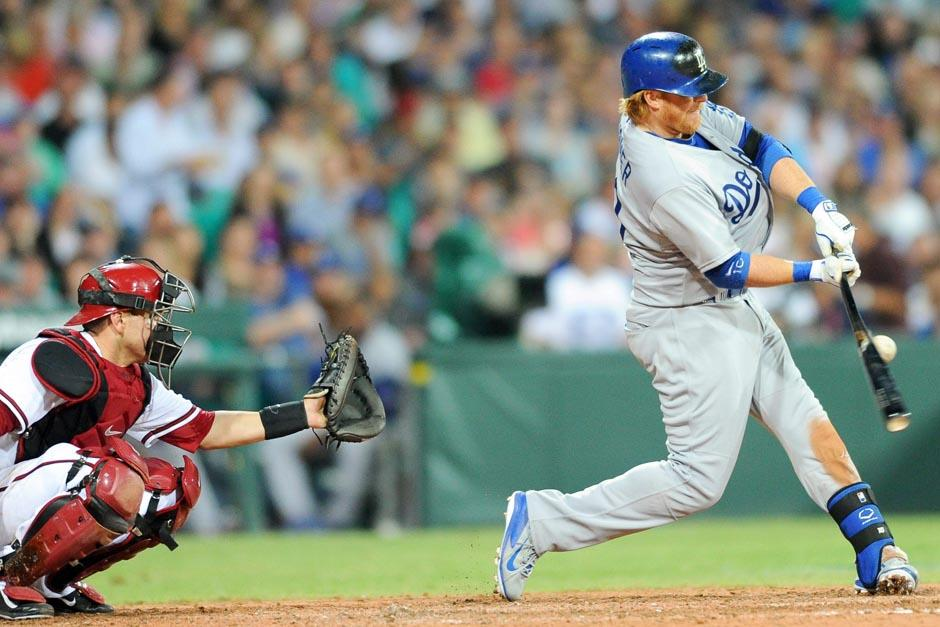 Justn Turner golpea una pelota durante el juego de apertura entre Los Ángeles Dodgers y los Diamondbacks de Arizona
