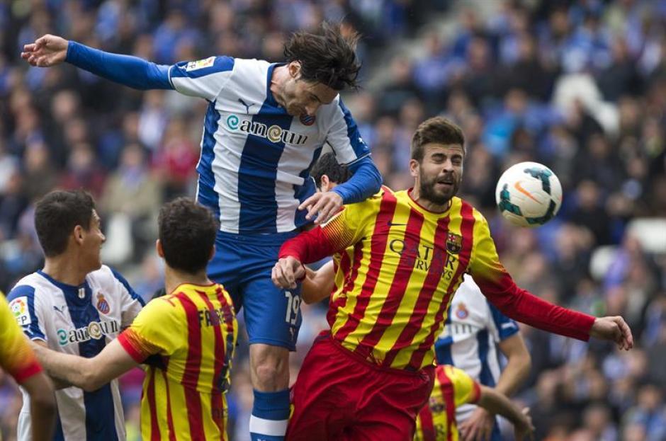 El defensa del Espanyol Diego Colotto remata de cabeza ante el defensa del FC Barcelona Gerard Piqué. (Foto: EFE)