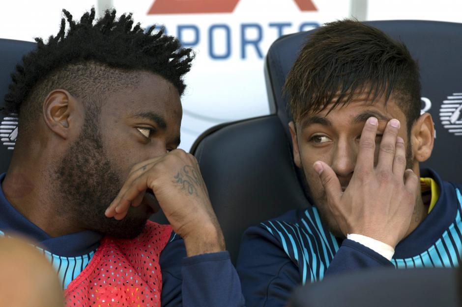 Los jugadores del Barcelona, el brasileño Neymar da Silva (d) y el camerunés Alexandre Song en el banquillo durante el partido correspondiente a la trigésimo segunda jornada de Liga que disputan frente al Betis en el Cam Nou. (Foto: EFE)