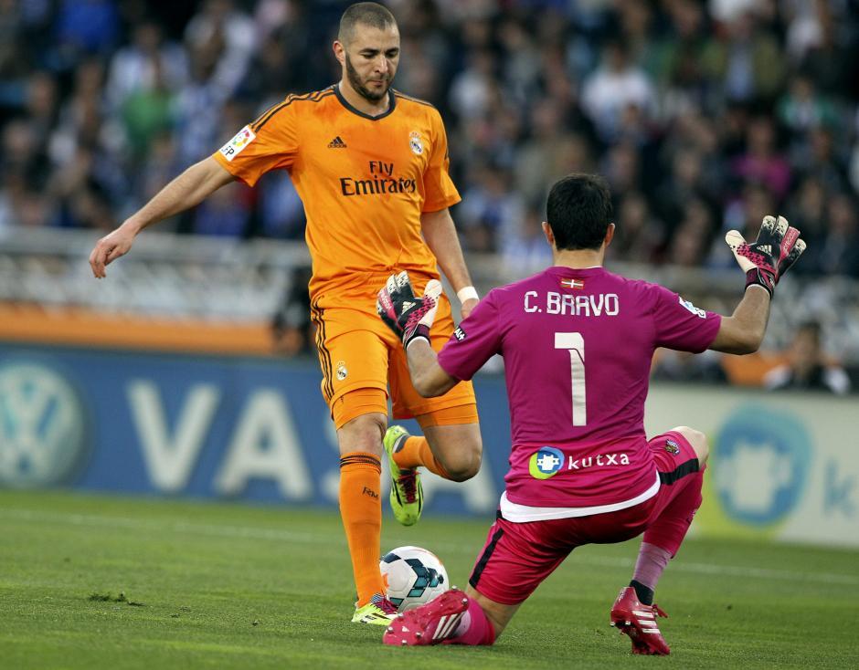 El portero de la Real Sociedad, Claudio Bravo (d), defiende al francés Karim Benzema, del Real Madrid, durante el partido, correspondiente a la trigésimo segunda jornada de Liga en Primera División, que se disputó esta tarde en el estadio de Anoeta, en San Sebastián. (Foto: EFE)