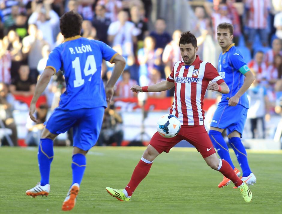 El delantero del Atlético de Madrid David Villa (2d) intenta controlar el balón ante el centrocampista del Getafe Pedro León (i). (Foto: EFE/Victor Lerena)