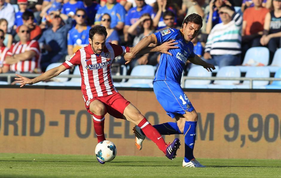 El defensa del Atlético de Madrid Juanfran (i) lucha un balón con el centrocampista del Getafe Pedro León. (Foto: EFE/Victor Lerena)