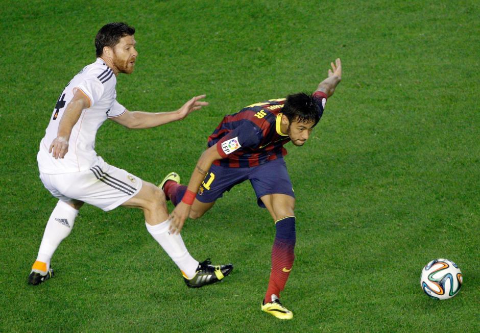 El delantero brasileño del FC Barcelona Neymar jr. (d) disputa un balón con el centrocampista del Real Madrid Xabi Alonso (i), durante el partido de la final de la Copa del Rey, que ambos equipos disputaron en el estadio Mestalla, en Valencia. (Foto: EFE)