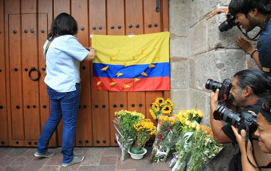 Una ciudadana colombiana coloca una bandera de su país en el portón de la casa del escritor colombiano Gabriel García Márquez, en Ciudad de México. (Foto: EFE/Mario Gúzman)