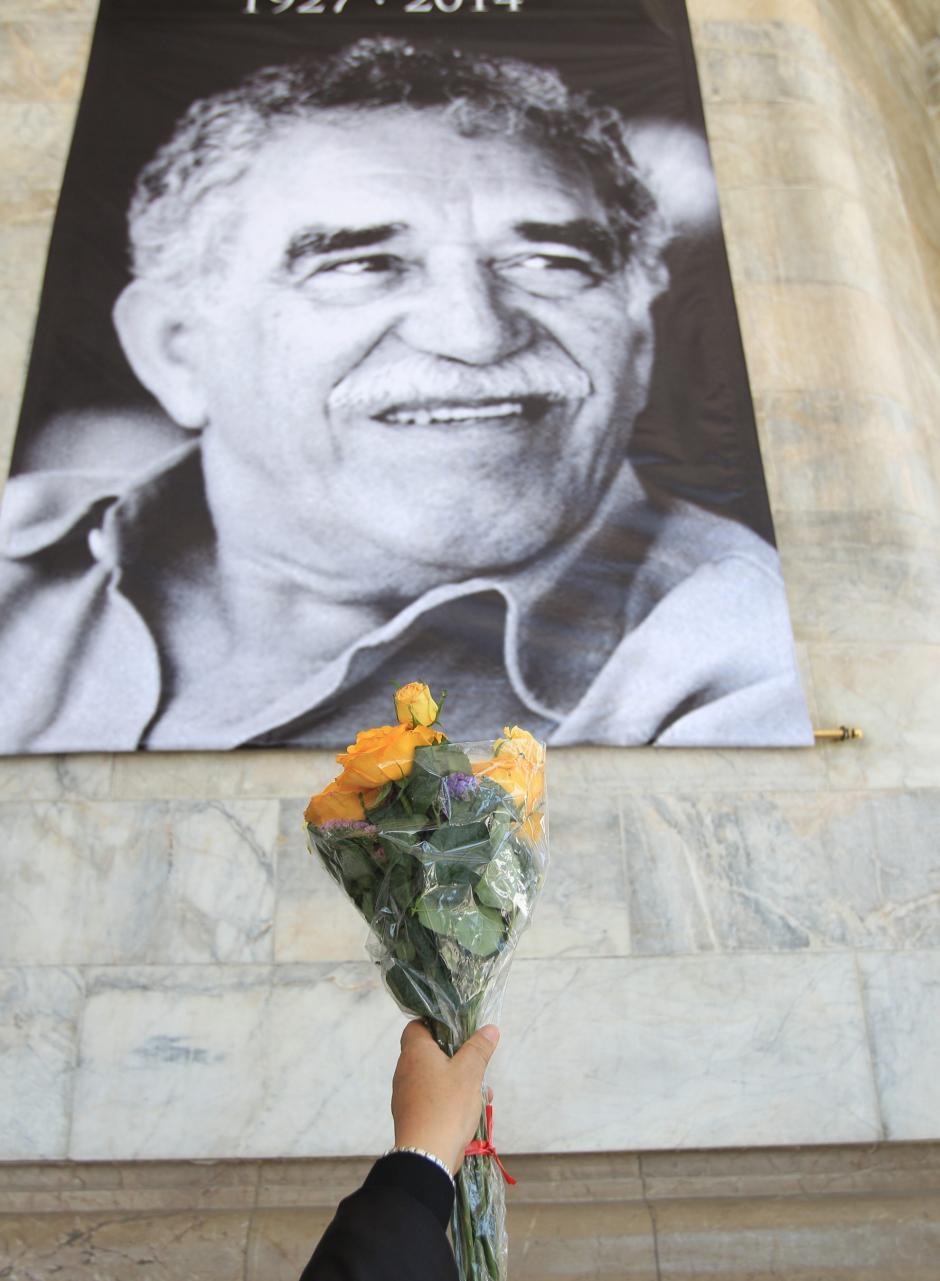 Un asistente ofrece un ramos de flores amarillas, frente a una imagen del fallecido escritor colombiano Gabriel García Márquez en el Palacio de Bellas Artes de Ciudad de México (México), donde se lleva a cabo un homenaje al Nobel, fallecido el pasado jueves. (Foto: EFE/ Mario Guzmán)