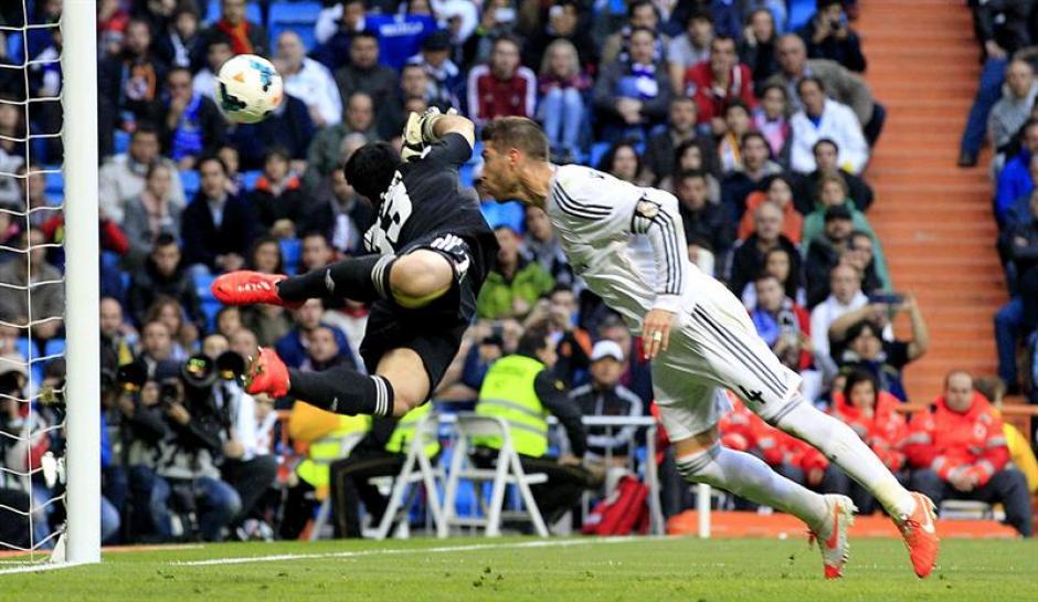 El defensa del Real Madrid Sergio Ramos (d) remata ante Andrés Fernández, portero de Osasuna, durante el partido de Liga en Primera División que se disputó esta tarde en el estadio Santiago Bernabéu, en Madrid. (Foto: EFE/Alberto Martín)
