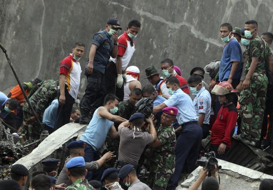 Varios miembros del servicio de rescate evacúan el cuerpo de una de las víctimas del accidente aéreo ocurrido en Medan, Indonesia. (Foto: EFE)