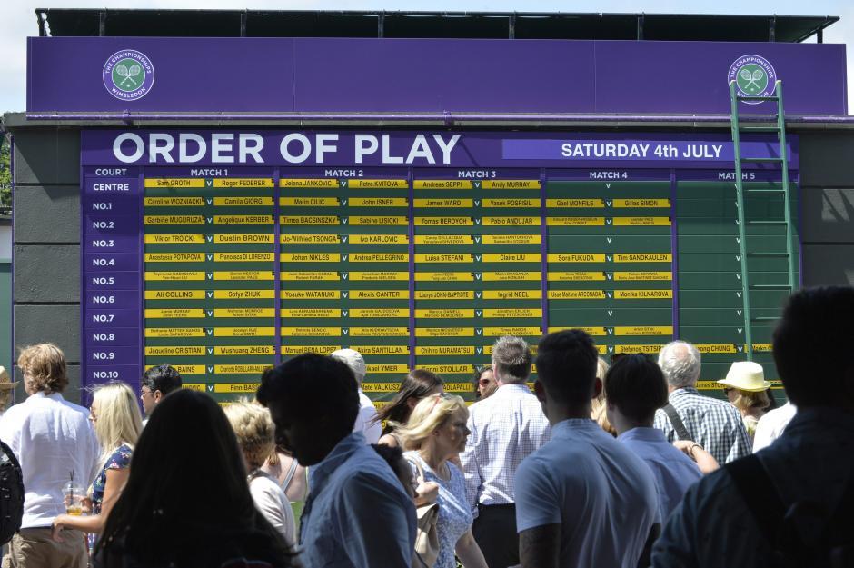 Los aficionados que asistieron al torneo de Wimbledon observan el calendario de juegos para este torneo que es uno de los más prestigiosos del circuito. (Foto: EFE/GERRY PENNY)
