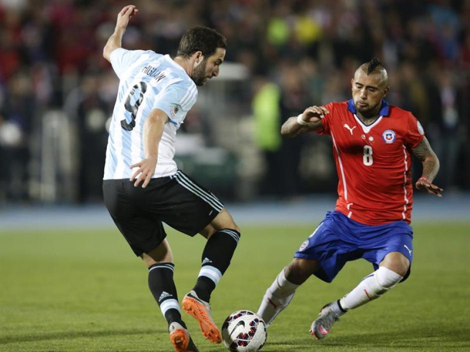 Gonzalo Higuaín con el balón, y defiende Arturo Vidal. (Foto: EFE)