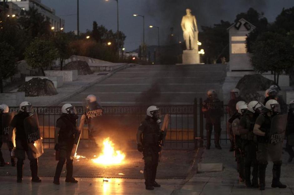 Agentes de policía evitan las bombas incendiarias lanzadas por manifestantes en Grecia. (Foto: EFE)