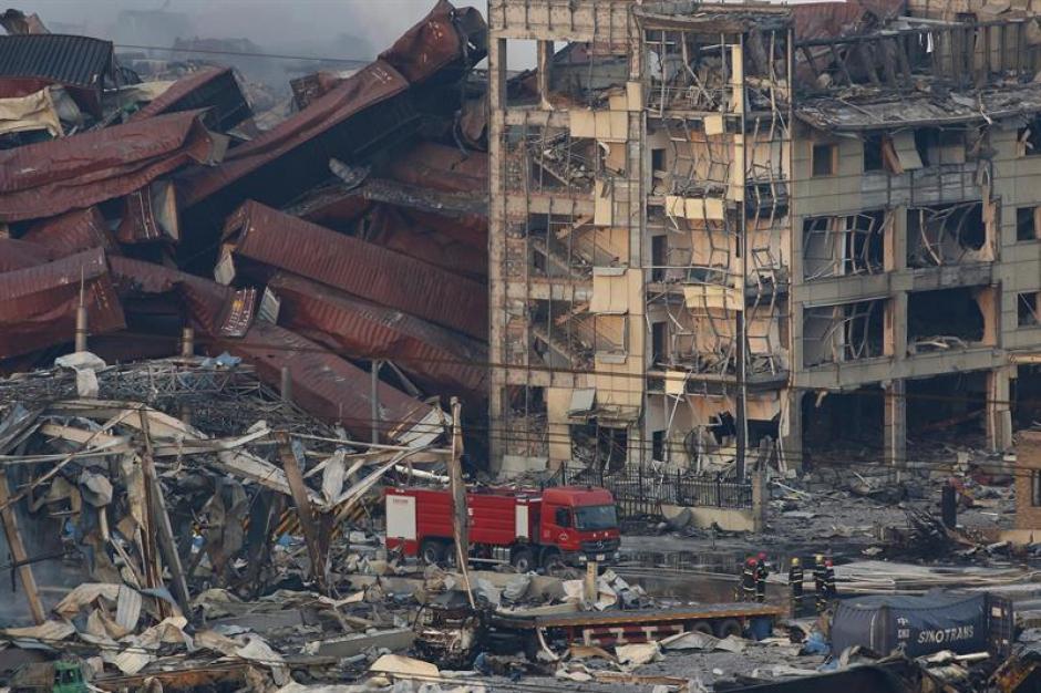 Miembros de los servicios de rescate trabajan entre cientos de vehículos quemados y varios edificios destruídos tras varias explosiones en China. (Foto: EFE)
