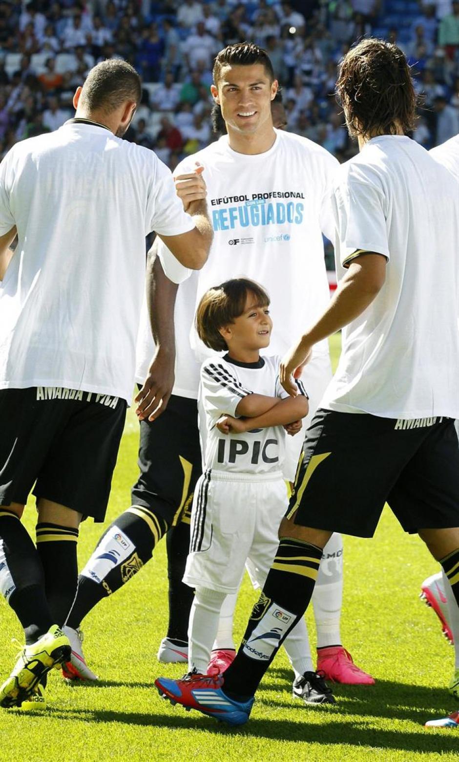 Zaid Abdul, el niño refugiado sirio, en el césped del Santiago Bernabéu vestido con la equipación del Real Madrid junto a Cristiano Ronaldo. (Foto: EFE)