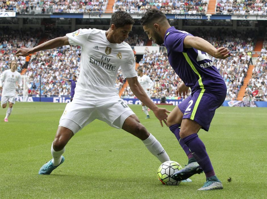 El defensa francés del Real Madrid Raphael Varane, pelea un balón con el centrocampista marroquí del Málaga Adnane Tighadouini en partido de la sexta jornada de liga en Primera División, esta tarde en el estadio Santiago Bernabéu. EFE/Chema Moya