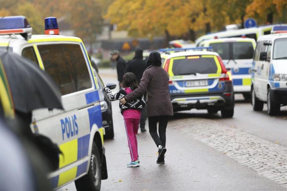 Alumnos acordonan el colegio Kronan junto a sus padres después de que un hombre enmascarado atacara a varias personas con una espada antes de que la policía sueca le disparara. (Foto: EFE)
