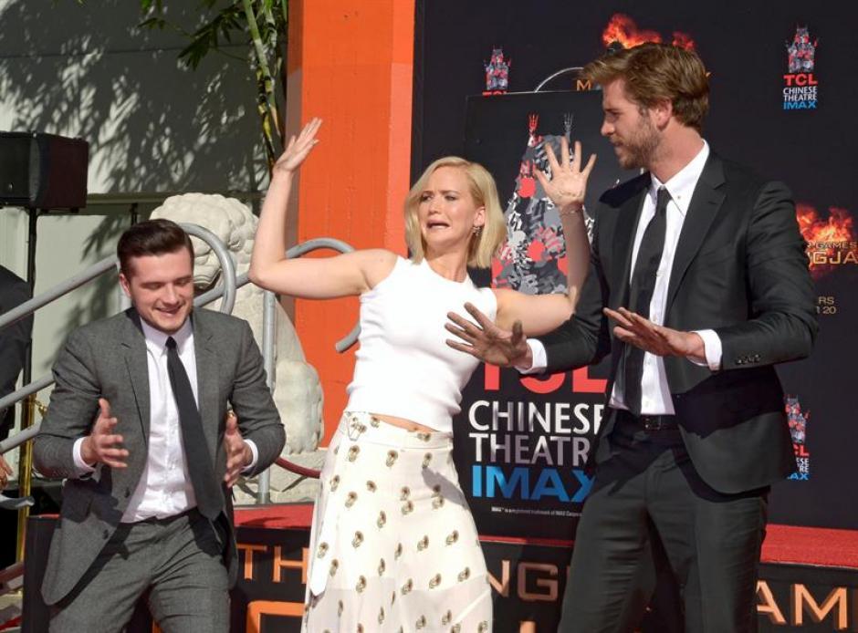 Los actores, Josh Hutcherson, Jennifer Lawrence y Liam Hemsworth hacen gestos con las manos cubiertas con cemento fresco, luego de imprimir sus huellas frente al mítico Teatro Chino en la ciudad de Hollywood en California. (Foto: EFE)