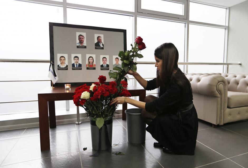 Una mujer coloca flores junto a las fotografías de sus compañeros, integrantes de la tripulación del vuelo de la aerolínea Kogalymavia, siniestrado el sábado en el Sinaí. (Foto: EFE)
