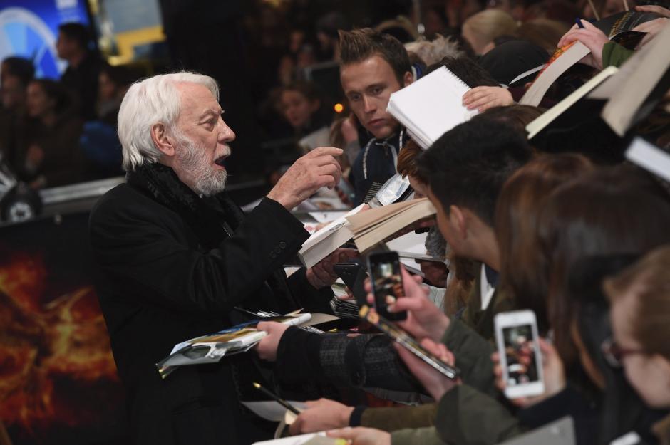 """El actor canadiense Donald Sutherland firma autógrafos a su llegada al estreno de """"Los Juegos del Hambre: Sinsajo - Parte 2"""", en Berlín, Alemania. (Foto: EFE/Britta Pedersen)"""