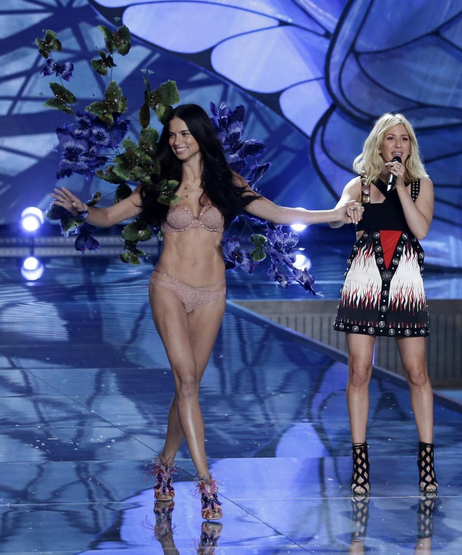 La modelo brasileña Adriana Lima (i) camina por la pasarela mientras la cantante británica Ellie Goulding (d) se presenta durante el desfile de la marca Victoria's Secret hoy. (Foto: EFE/Jason Szenes)