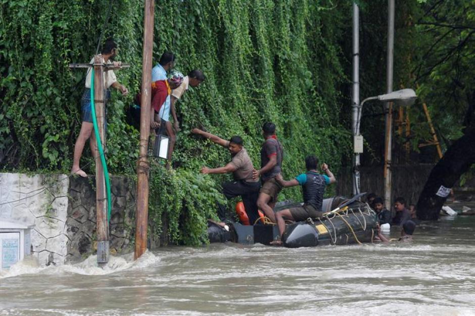 Miembros de la policía rescatan a un grupo de personas de las inundaciones en Chennai, India. (Foto: EFE)