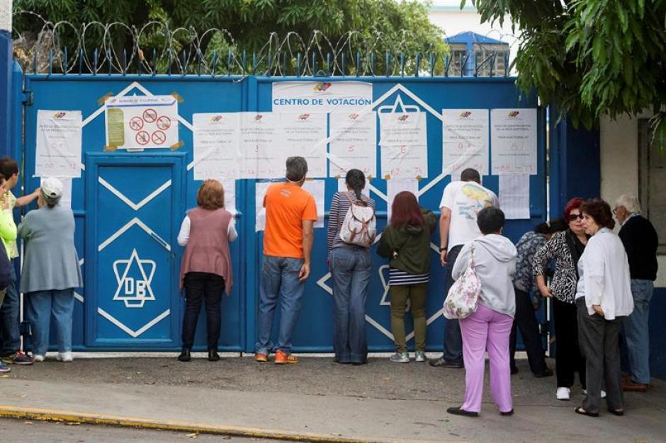 Los venezolanos antes de ingresar al centro de votación, revisan el listado de nombres para confirmar su participación. (Foto: EFE)